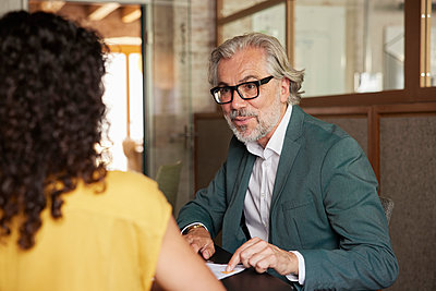 Bearded male professional explaining business plan to female colleague in office - p300m2299876 by Rainer Berg