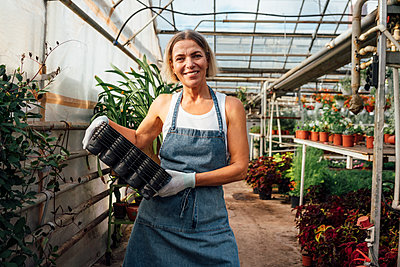 Female agriculture worker carrying seedling trays while standing at plant nursery - p300m2300537 by Vasily Pindyurin