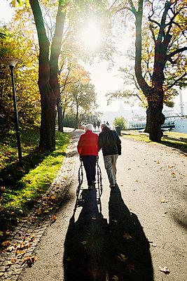 Sweden, Stockholm, Skeppsholmen, Rear view of senior woman and mature man walking in park - p352m1186958 by Lena Katarina Johansson