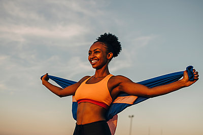 Smiling female athlete with arms outstretched against sky - p426m2270745 by Maskot