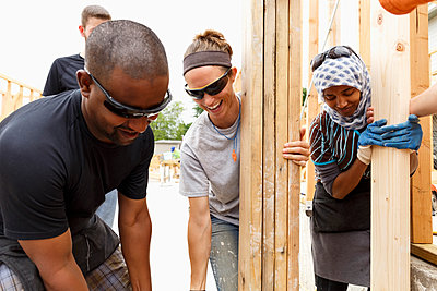 Volunteers holding lumber at construction site - p555m1522817 by Roberto Westbrook