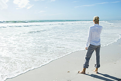 Woman standing barefoot on beach - p6241802f by Sigrid Olsson