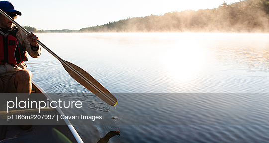 Man paddling canoe in the morning on a misty lake in Ontario, Canada. - p1166m2207997 by Cavan Images