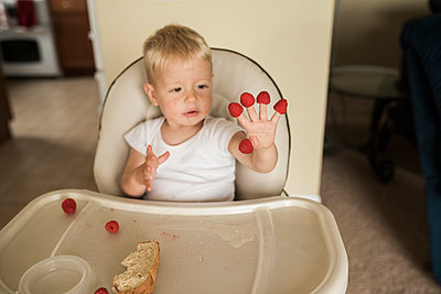 Baby boy with raspberries in fingers sitting on high-chair at home - p1166m1543958 by Cavan Images