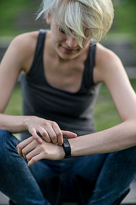 Smiling young woman checking her smartwatch - p300m1205052 by A. Tamboly