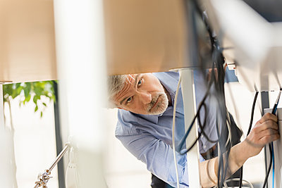 Businessman sorting wire tangle - p300m1587465 von Jo Kirchherr