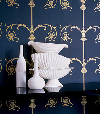 Blue and gold patterned wallpaper with black shelf displaying white ceramic homeware - p349m695208 by Emma Lee