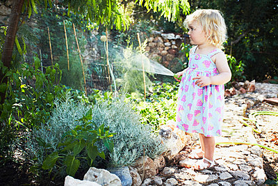 Portrait of a Young girl gardening - p429m1450552 by Liam Norris