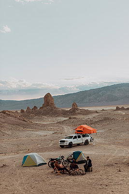 Motorcyclist road trippers around camp fire, Trona Pinnacles, California, US - p924m2068171 by Peter Amend