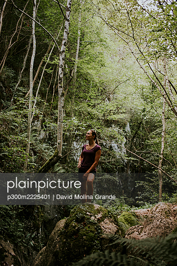 Woman surrounded by green trees exploring forest - p300m2225401 by David Molina Grande