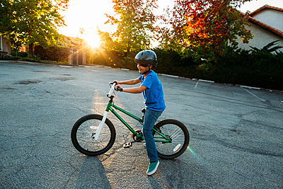 Boy wearing cycling helmet while riding bicycle during sunset - p1166m1508161 by Cavan Images