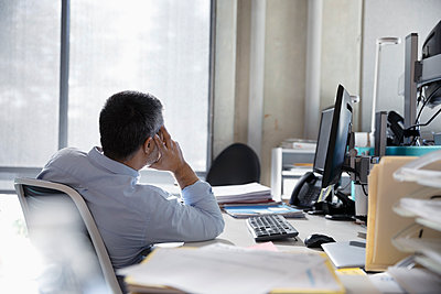 Thoughtful businessman at office desk - p1192m2062438 by Hero Images