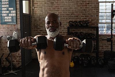 Senior man exercising with dumbbells in the fitness studio - p1315m2018221 by Wavebreak