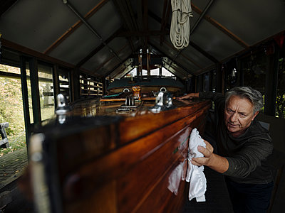 Senior man cleaning wooden boat in a boathouse - p300m2156107 by Gustafsson