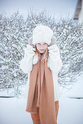 Portrait of young woman in fur hat - p312m1121641f by Christina Strehlow