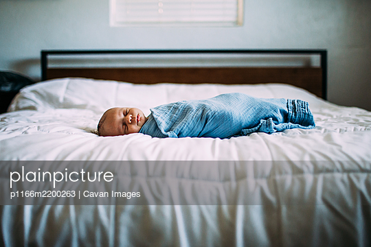 center portrait of newborn sleeping on bed - p1166m2200263 by Cavan Images