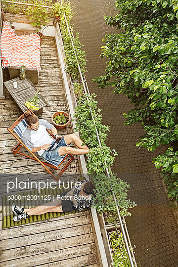 Young couple relaxing on their balcony in summer, man using tablet - p300m2081125 von Peter Scholl