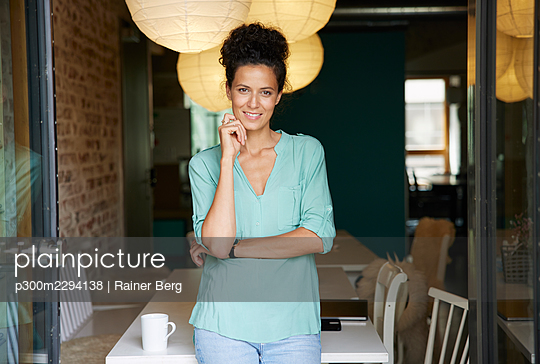 Smiling female professional standing at workplace - p300m2294138 by Rainer Berg