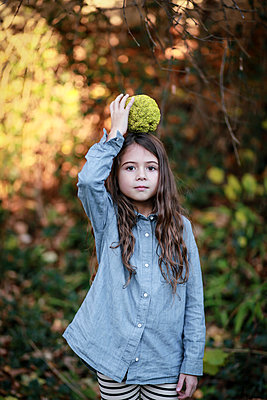 Kid Playing with Hedge Apple in Autumn  - p1019m1122379 by Stephen Carroll