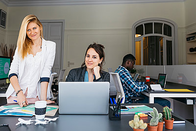 Young businesswomen working together, using laptop, colleague sitting in background - p300m1460268 by Josep Rovirosa