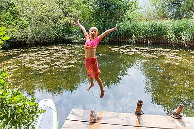 Carefree girl jumping into pond - p300m2030479 by Tom Chance