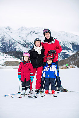 Portrait of family in ski-wear standing together against mountain range - p426m803141f by Maskot