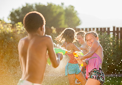 Children squirting each other with water guns - p555m1479000 by Mike Kemp
