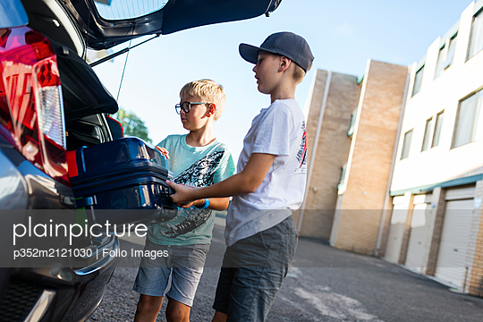 Boys unloading suitcase from car boot - p352m2121030 by Folio Images
