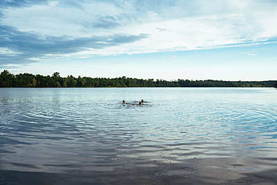 Mid distance view of female friends swimming in lake against sky - p1166m2025278 by Cavan Images