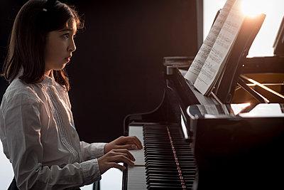 Adorable schoolgirl playing piano in music school - p1315m2003042 by Wavebreak