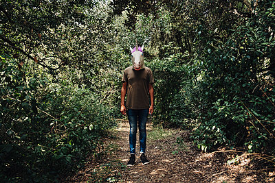 Man with a unicorn mask on the woods - p1423m2086983 von JUAN MOYANO