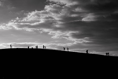 Unrecognizable people walking by the crest of a dune - p1423m2092602 by JUAN MOYANO
