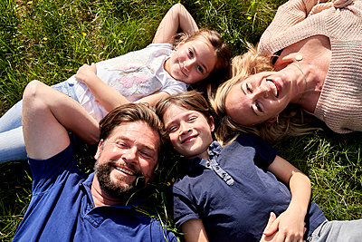 Happy family lying on grass during sunny day - p300m2197439 by Stefanie Aumiller