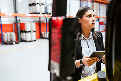 Female professional looking away while holding digital tablet at illuminated warehouse - p300m2267037 by DREAMSTOCK1982