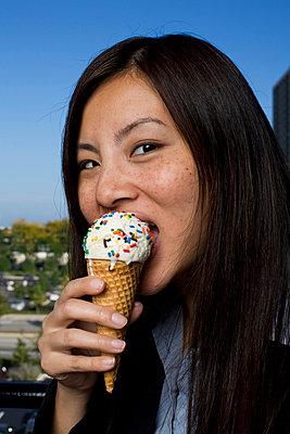 Businesswoman eating ice cream, close-up - p3722669 by James Godman