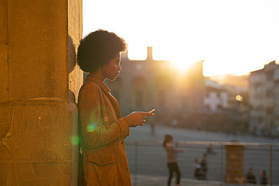 Young woman with afro hair using smartphone, leaning against stone wall, Florence, Toscana, Italy - p429m2127255 by Lorenzo Antonucci