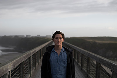 Young man standing on bidge - p552m1169782 by Leander Hopf