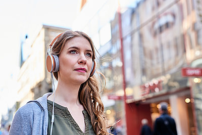 Woman with headphones in pedestrian zone - p890m1440023 by Mielek