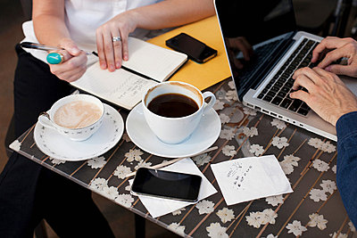 Businesspeople in cafe, man using laptop woman writing - p924m699256f by Samantha Mitchell