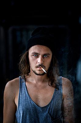 Man smoking cigarette - p966m890906 by Tobias Leipnitz