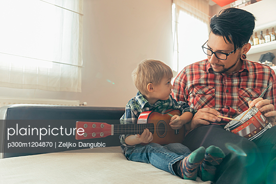 Father and son playing toy musical instruments - p300m1204870 by Zeljko Dangubic
