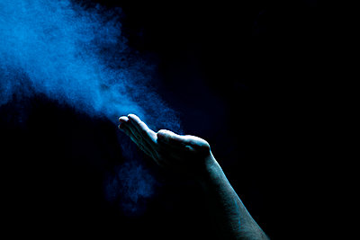 hand blowing dust - p1165m956395 by Pierro Luca