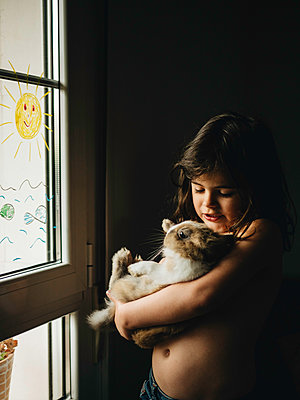 Little girl carries rabbit in her arms at the window  - p1522m2176539 by Almag