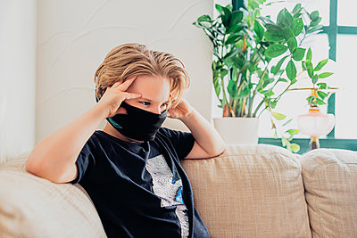 Boy sitting on couch in living room at home wearing a mask - p300m2189012 by Jana Mänz