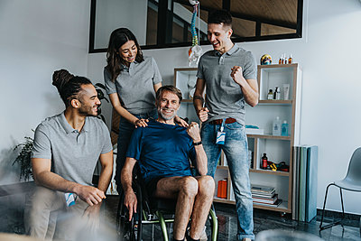 Physiotherapists cheering patient sitting on wheelchair in practice - p300m2276827 by Mareen Fischinger