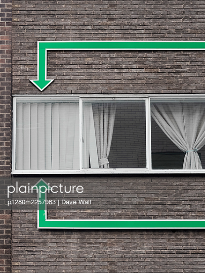 Windows and huge green arrows on brick house wall - p1280m2257983 by Dave Wall