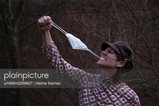 Woman making fun with her mask - p1650m2259627 by Hanna Sachau