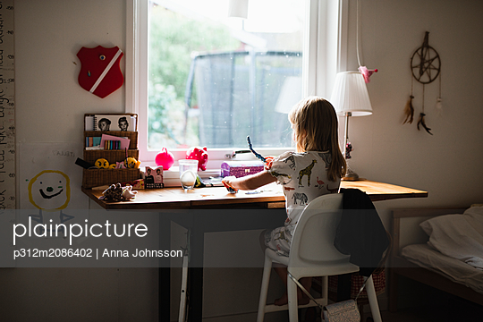 Girl sitting at desk - p312m2086402 by Anna Johnsson