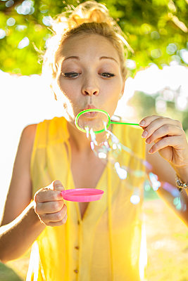 Beautiful blonde girl blowing bubbles and having fun in park - p1166m2071931 by Cavan Images