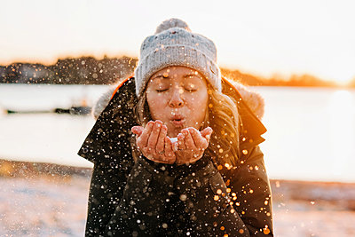 Woman blowing golden snow at sunset in winter - p1166m2153680 by Cavan Images